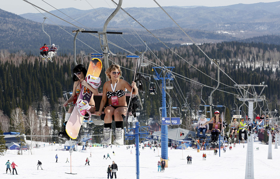 "Women ride a lift during a ""downhill ski and snowboard descent in swimwear"" event in central Siberia, April 18, 2015."