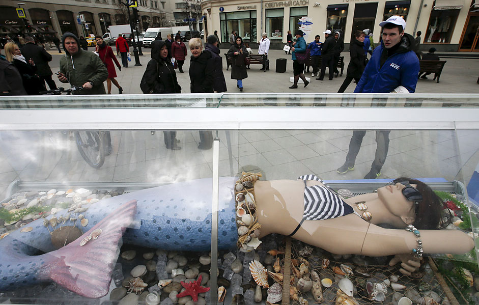 People look at a dummy of a seamaid which is on display near a streetfish market in central Moscow.