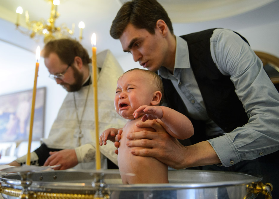 A baby being baptized at the Church of St. Seraphim of Sarov in Yekaterinburg.
