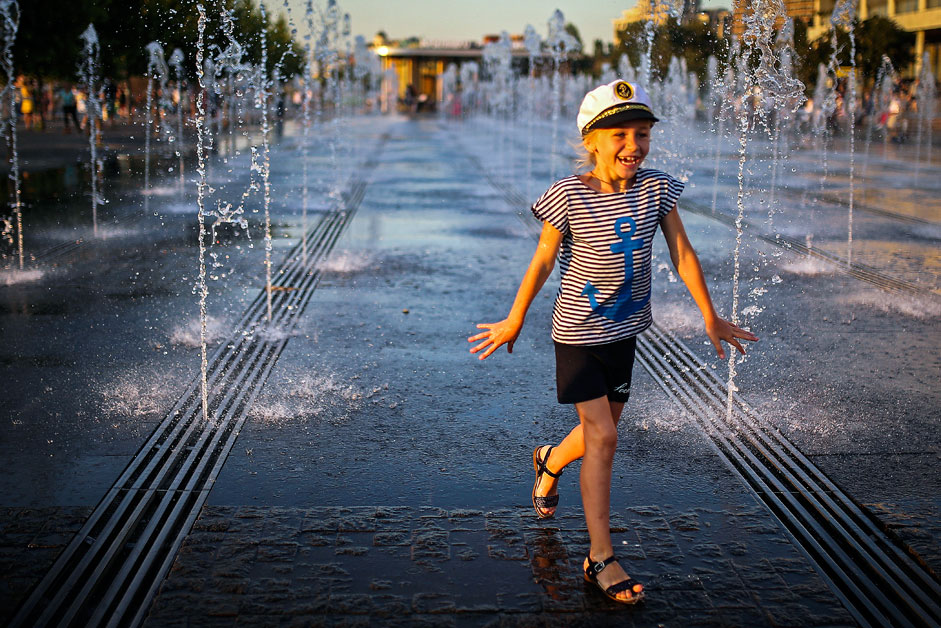 A child cools off in fountains in Muzeon Park in central Moscow in hot weather.