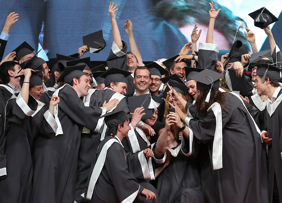 Russia's Prime Minister Dmitry Medvedev (C) congratulates first graduates of Skolkovo Institute of Science and Technology during the 2015 Startup Village conference, at the Skolkovo Innovation Center.