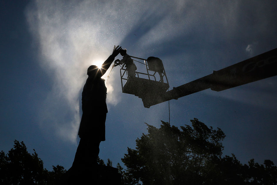 A worker washes a monument to famous Russian poet Aleksander Pushkin during preparations to celebrate the 216th anniversary of his birth in St. Petersburg, June 3, 2015.