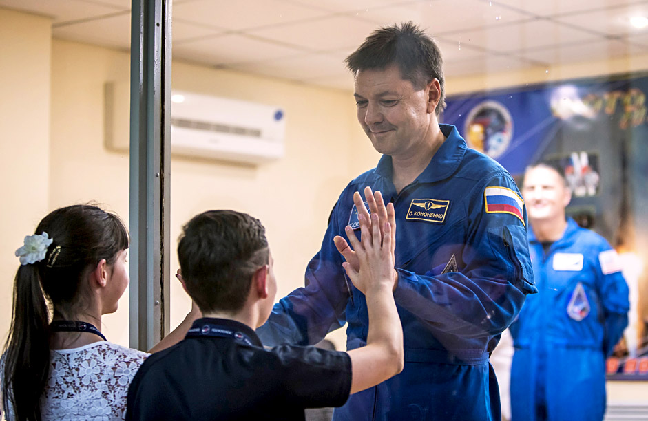 The ISS crew member Oleg Kononenko of Russia interacts with his children as he stands behind a glass wall at a news conference at the Baikonur cosmodrome in Baikonur, Kazakhstan, July 21, 2015. The crew is scheduled to travel on board the Soyuz spacecraft on July 23, 2015.