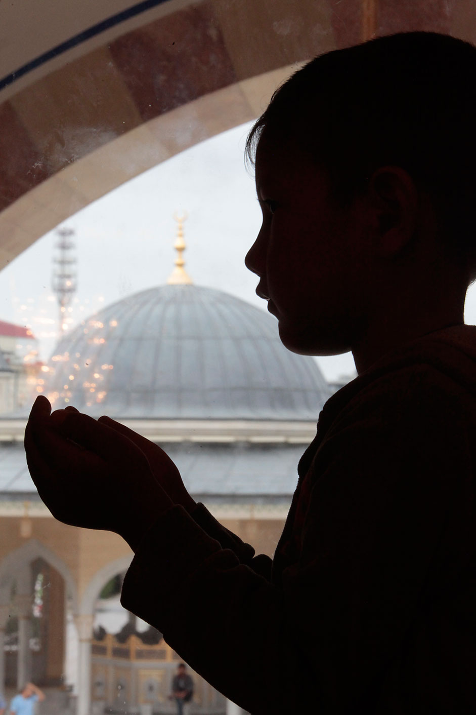 A Chechen boy performs an Eid al-Fitr prayer to mark the end of theholy fasting month of Ramadan in Chechen capital of Grozny, Russia,Friday, July 17, 2015. Eid al-Fitr prayer marks the end of the holyfasting month of Ramadan.