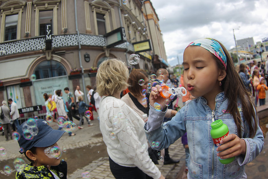 A girl blows bubbles as she participates in the Dreamflash 2015 bubble parade.