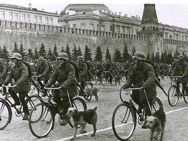 Platforms were set up near the main administrative building from where war veterans,  stakhanovites and the Communist Party heads gave speeches / Parade on Red Square, Moscow, May 1, 1938, Military dog handlers on bicycles