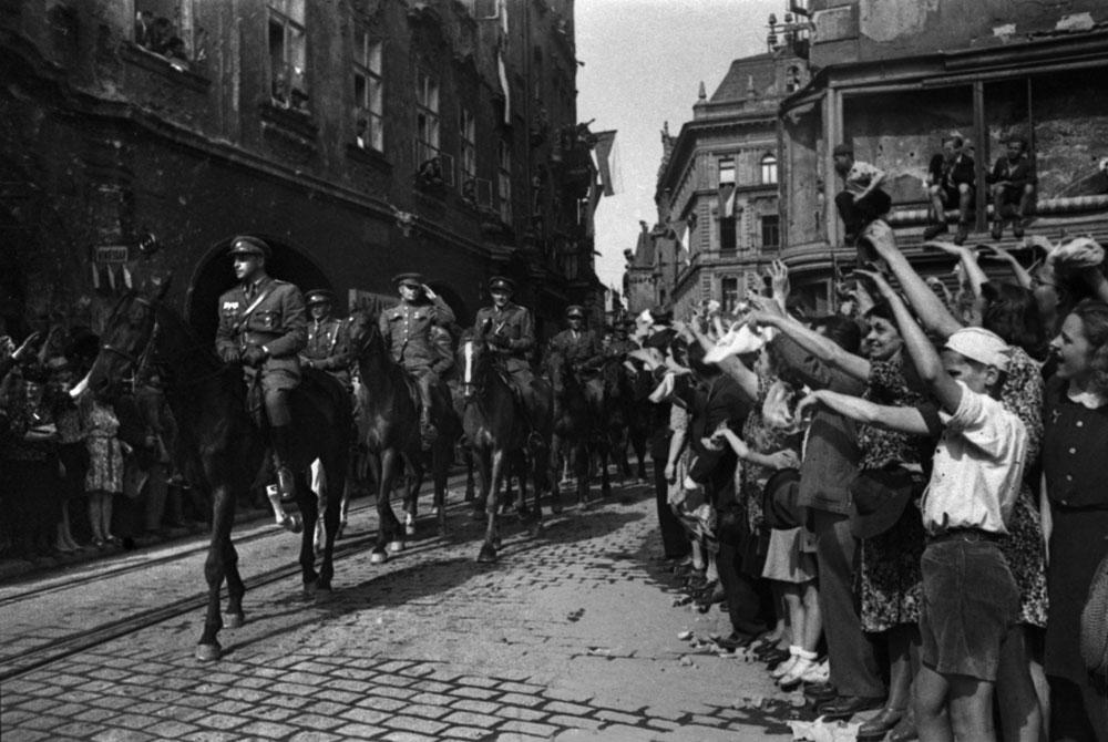 Nelle sue prime fotografie di Stalingrado del 1942 il respiro della guerra si percepisce in tutto. Nelle ultime invece ogni inquadratura è impregnata dell'aria della vittoria. Dopo la battaglia di Stalingrado Evzerichin fu insignito dell'ordine della Stella Rossa e della medaglia 'Alla difesa di Stalingrado' (testo tratto dall'introduzione di Valerij Stigneev 'La russia ai tempi di Stalin nelle fotografie di Emmanuil Evzerichin') //Praga. Gli abitanti della città salutano le truppe degli alleati. Maggio 1945