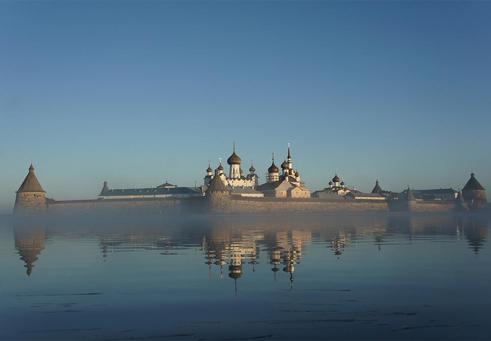 """Mit ihrem auf der UNESCO-Liste eingetragenen Kloster und ihren unberührten Wäldern und Seen sind die  Solowetzki-Inseln ein Ort fast himmlischer Schönheit. Jahrhundertelang beheimateten die Inseln ein abgelegenes Kloster, aber 1920 wurde auf Anweisung von Lenin ein Gulag, das """"Solowetzki-Lager zur besonderen Verwendung"""" dort errichtet. Es war ein Ort, an dem Kriminelle und Personen, die sich gegen die Ideologie der jungen Sowjetunion stellten, sich durch harte Arbeit """"rehabilitieren"""" sollten. In den frühen 1990er Jahren wurde das Kloster mit einer Ausstellung im ersten Stock wiedereröffnet, die an die moralische Katastrophe, die während der Zeit der Gulags über die Sowjetunion hereinbrach, in all ihrer Grausamkeit erinnert."""