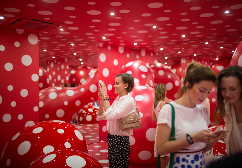 """Обратното, инсталацията """"Пътепоказател на вечния космос"""" (2015) кани зрителите в една среда, където стените и структурите са покрити с точки на червен фон, оформяйки неземен пейзаж, който обърква възприятията и пространствената им ориентация."""