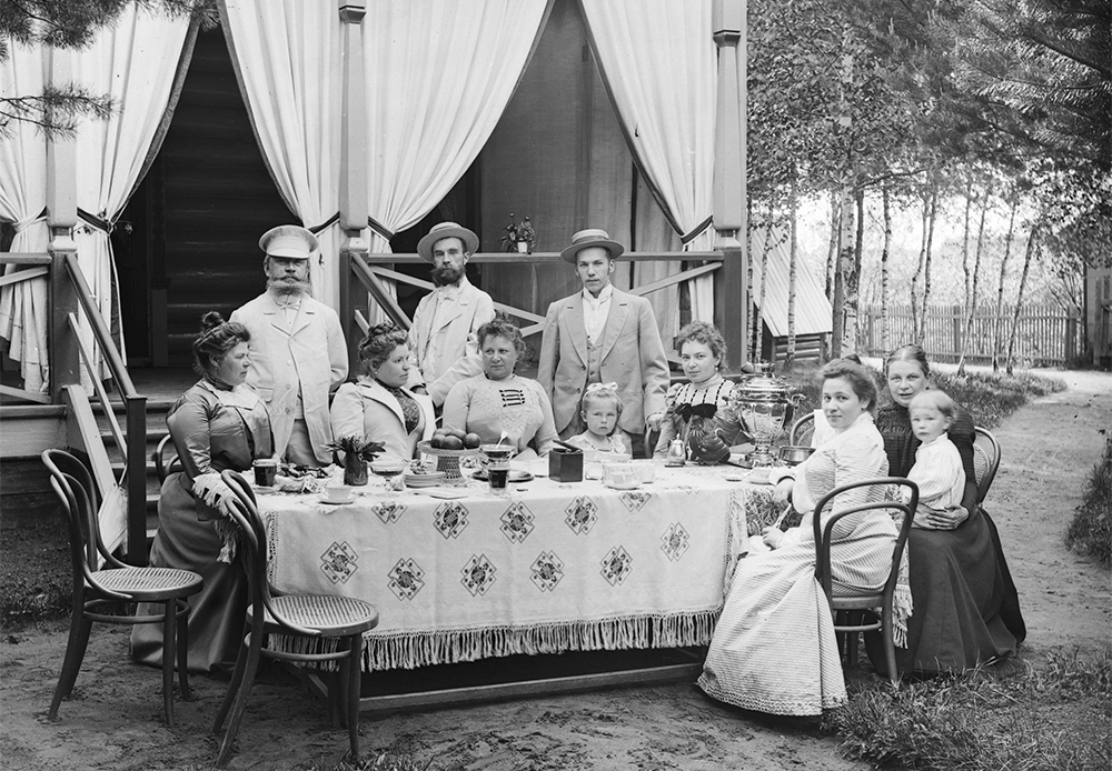 In summer, many Russian city dwellers escape to the dacha — rural cottages that occupy a deep place in the national psyche. / Family tea-drinking at the dacha, 1901.
