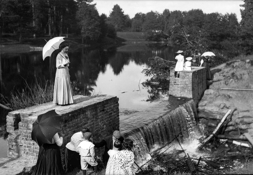 In the early Soviet era, only cultural and scientific luminaries and top officials were given dachas. / Dacha inhabitants strolling around a stone dam, 1909.