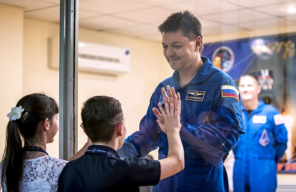 """Олег Кононенко, членът на екипажа на Международната космическа станция, който ще полети на кораба """"Съюз"""" на 23 юли, общува с децата си чрез стъклена стена по време на прес-конференцията на космодрума Байконур."""