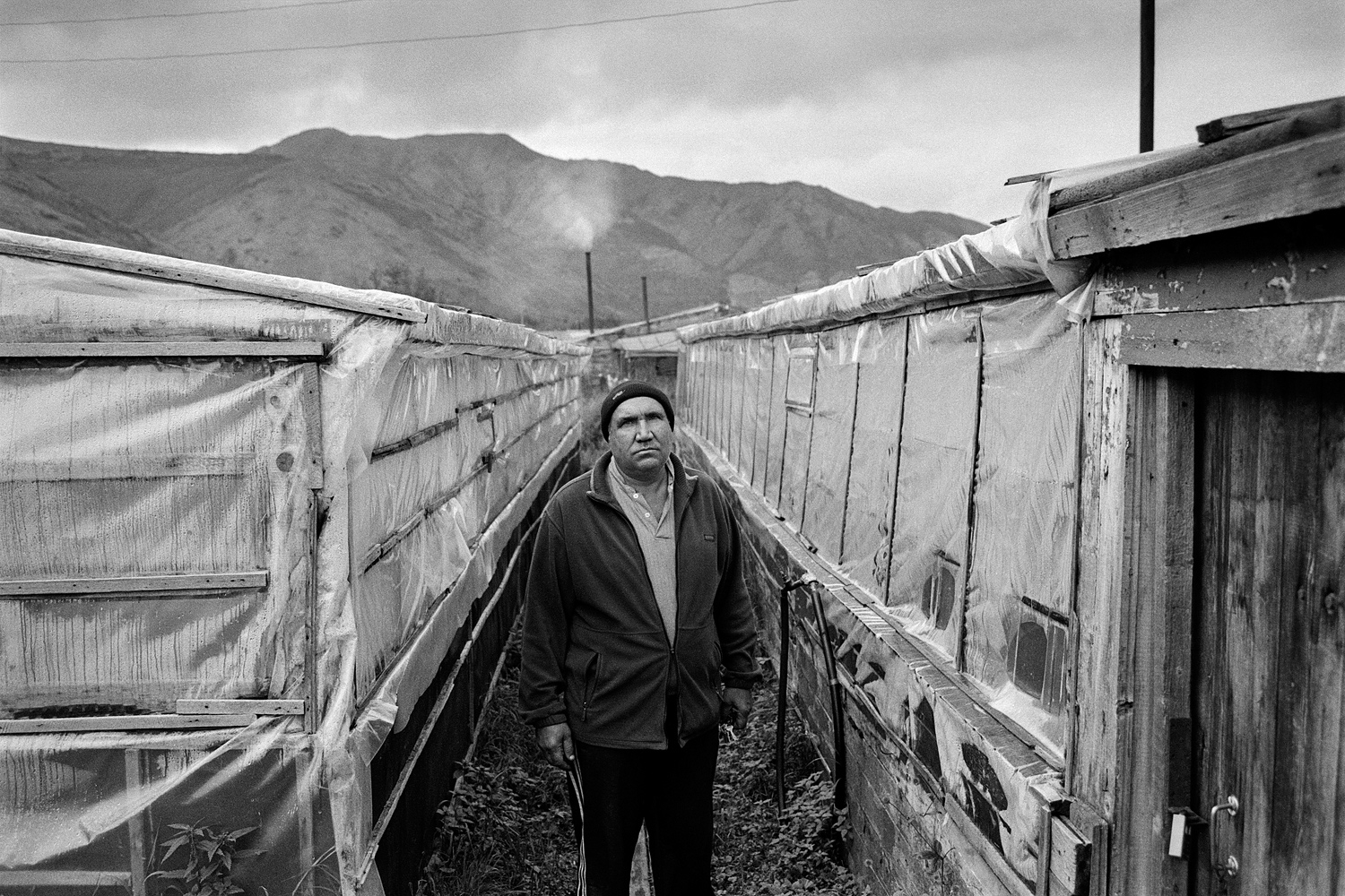In 1995 the Karamken mining and processing plant was closed down. In 2012 Karamken lost its status of urban-type settlement, and is now in the resettlement list. Valeriy is one of the few remaining residents. He cultivates cucumbers in greenhouses heated with firewood.
