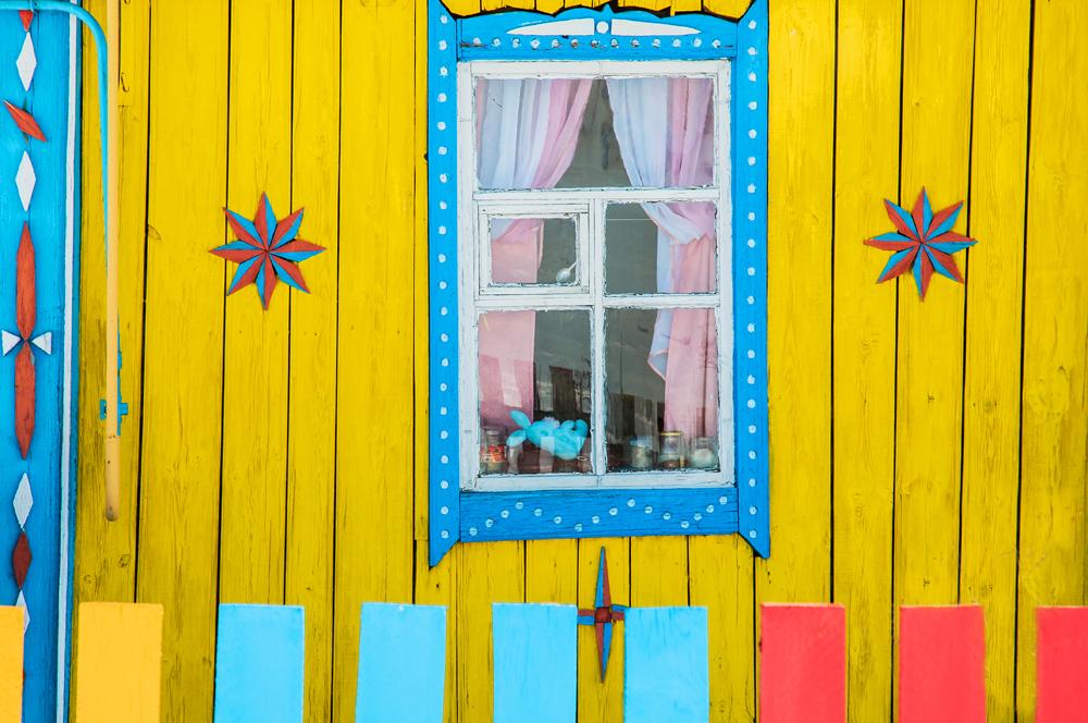 In keinem Dorf gleicht ein Haus dem anderen. Was für die Bewohner zählt, ist die individuelle Gestalt ihrer Hausfassade: je farbenfroher, desto größer die Chance, den unausgesprochenen Wettbewerb um das schönste Haus für sich zu entscheiden. //  Das Dorf Machmutowo