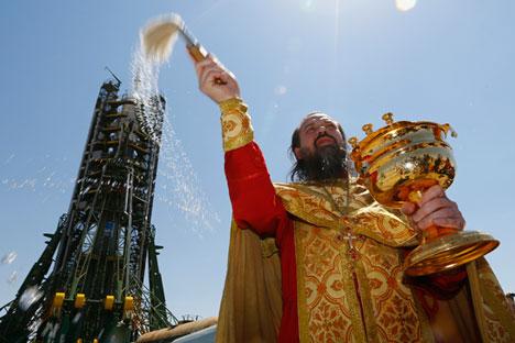 Orthodoxer Priester spricht einen Segen vor Sojus-Raumschiff TMA-13M aus, das vom Startplatz am Bajkonur-Kosmodrom absetzt.