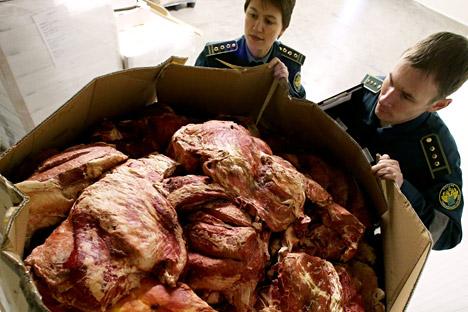 Zollbeamten durchsuchen in Beschlag genommenes Fleisch an der russisch-polnischen Grenze.