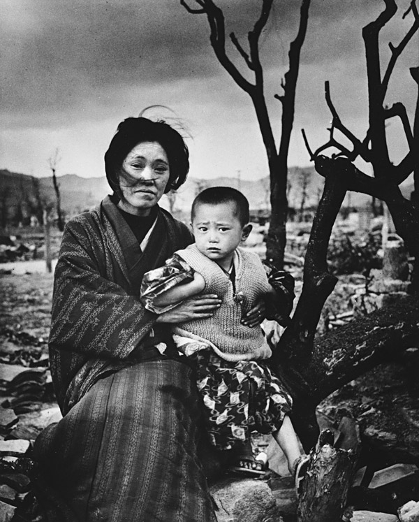 A mother and child, dressed in traditional clothing, sit on the ground amid rubble and brunt trees, Hiroshima, Japan, December 1945.