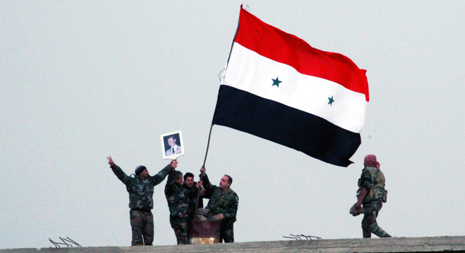 Syrian soldiers hold the national flag and photo of Syria President Bashar Assad atop a building at Deir al-Adas town in the southern province of Daraa, Syria, 11 February 2015. According to the official SANA, the Syrian army gained control over the strategically area of Deir al-Adas in Daraa province on 11 February