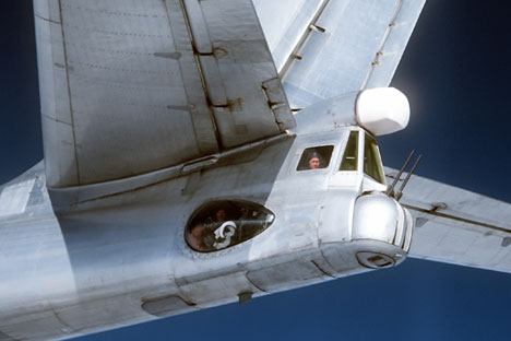 A radio-gunner in the Tu-95 Bear strategic bomber cockpit, photographed from an F4D Phantom fighter of the U.S. Air Force