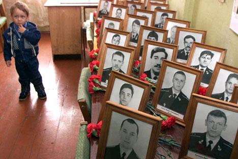 Un niño junto a los retratos de las víctimas del submarino Kursk, en sus barracas, durante la ceremonia conmemorativa en el puerto Ártico de Vidiádevo. Las familias de las víctimas se reunieron en Vidáyevo para recordar a los 118 hombres que perecieron hace 15 años en el naufragio del submarino nuclear ruso Kursk.