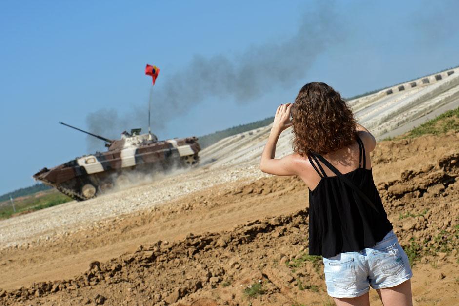 Espectadora toma fotos de un vehículo de combate del equipo venezolano durante la competición de BMP-2, em los Juegos del Ejército Internacionales.