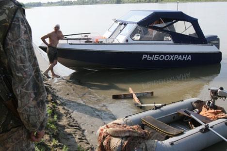 Policial conversa com caçador detido durante operação no rio Irtich