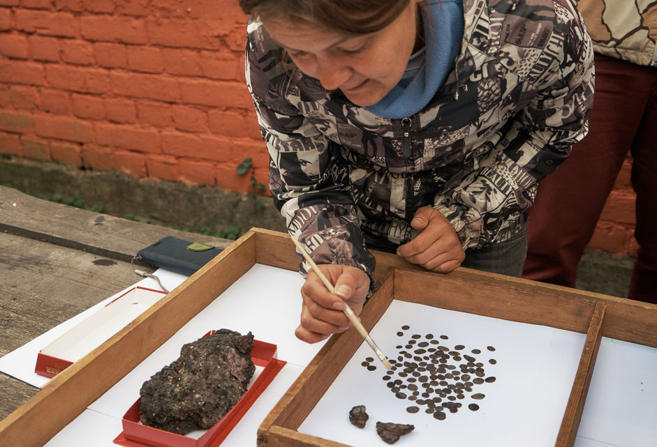 Deputy Head of the archaeological expedition Natalya Grigoryeva demonstrates a hoard of historical artifacts dating back to the times of Ivan the terrible and Boris Godunov -- 116 silver coins, a purse, and fragments of German ceramics. It was discovered during the restoration of the Old Ladoga Fortress in the village of the same name in the Leningrad Region.
