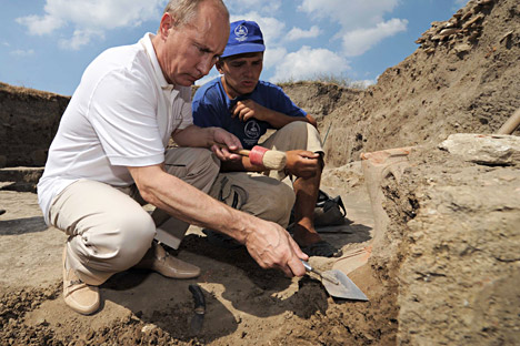 2011年8月10日、タマン半島。ウラジーミル・プーチン首相(左)が、古代ギリシャの都市ファナゴリアの発掘調査を行った考古学者のキャンプで、アンフォラをきれいにする。=