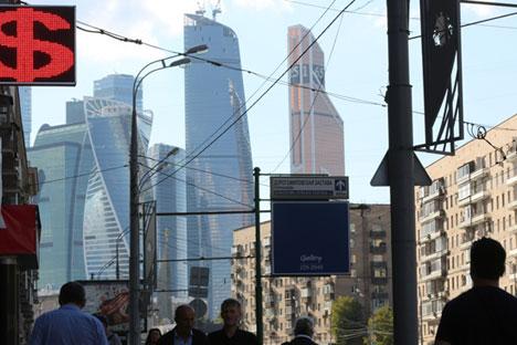 Sebuah gedung pencakar langit di daerah bisnis Moscow City, di belakang tempat penukaran uang, Moskow, Rusia (23/8). Rubel Rusia turun sebesar 2,3 pesen pada hari Senin dan menembus level terendah yang bertahan pada tujuh bulan terakhir mengikuti harga minyak, produk kunci ekspor Rusia.