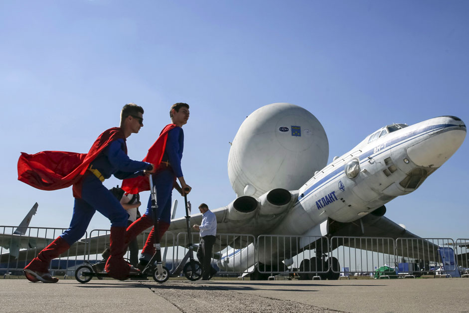 Promoters skate past a Myasishchev VM-T Atlant strategic airlift airplane on display at the MAKS International Aviation and Space Salon in Zhukovsky, outside Moscow, Russia, August 25, 2015