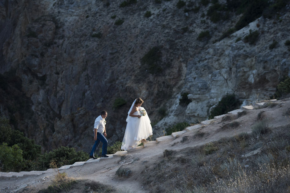 Wedding couple climbs to the Cape Fiolent in Crimea.