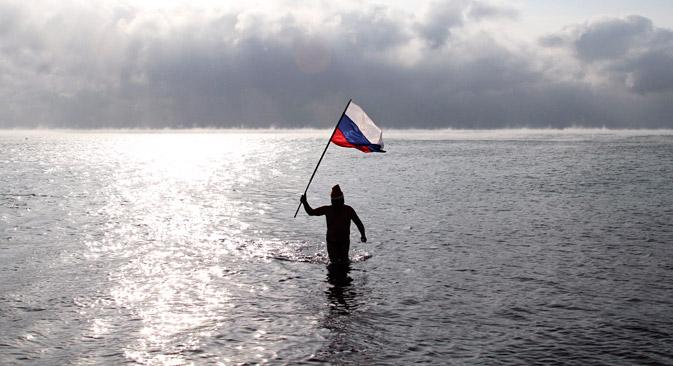Un homme tenant le drapeau russe marche dans la mer Noire près de Evpatoria, en Crimée.