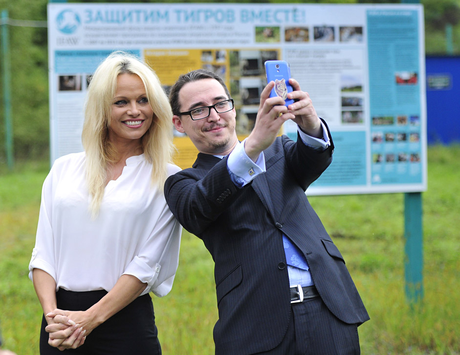 PRIMORYE TERRITORY, RUSSIA. SEPTEMBER 3, 2015. Canadian-American actress and animal rights activist Pamela Anderson (L) poses for a photograph with a man during her visit to a rehabilitation center for the animals affected by flood in Ussuriysk, Primorye Territory.
