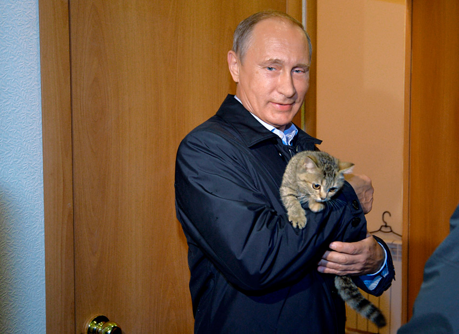 Russian President Vladimir Putin holds a cat as he inspects housing built for victims of wildfires in the village of Krasnopolye, in Khakassia, a region in southeastern Siberia, Russia, Friday, Sept. 4, 2015.