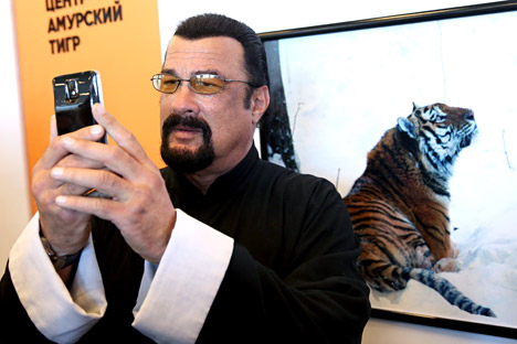 American actor Steven Seagal (C) takes a selfie an exhibition stand of the Amur Tiger Centre at the 2015 Eastern Economic Forum on Russky Island off Vladivostok, Russia on September 4, 2015