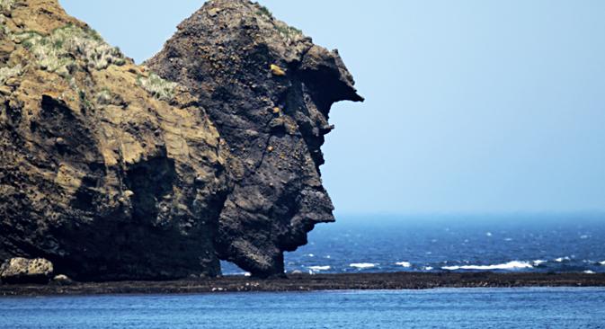 Pemandangan formasi batuan pesisir 'Orang yang Sedang Minum' (The Dringking Man) di Pulau Urup, Kepulauan Kuril, Laut Okhotsk, Sakhalin Oblast, Timur Jauh, Rusia.
