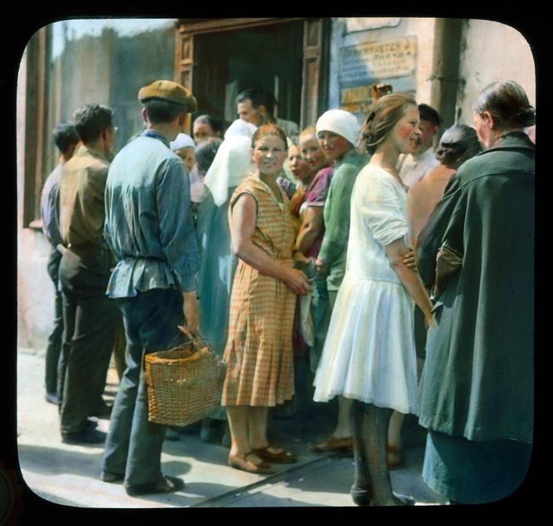 それぞれの旅行記には約150枚の手作業で色付けした映写用スライドと音楽に合わせた画像が含まれていた。彼はこのショーを「夢の写真」と呼び、「魅惑的なエンターテイメントの新たな形態」と宣伝した。/ モスクワ:食べ物を買うために通りに行列を成す人々のシーン、1931年。