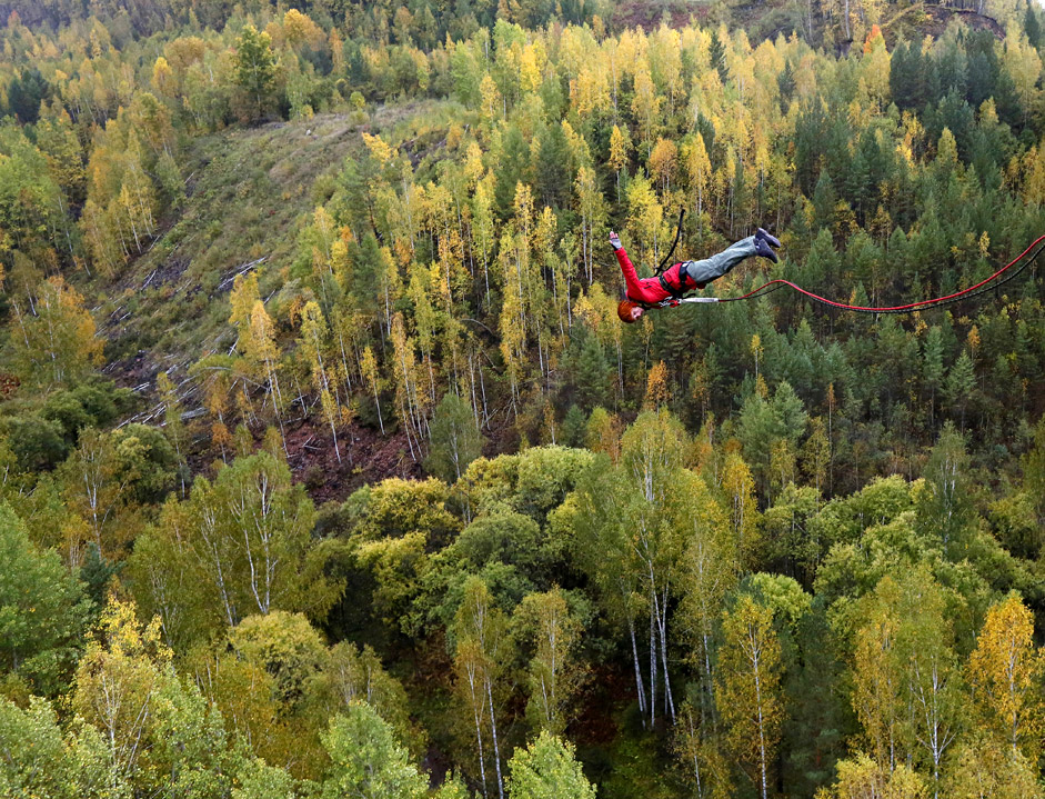 "A member of the ""Exit Point"" amateur rope-jumping group jumps from a 144-ft high waterpipe bridge in the Siberian Taiga area outside Krasnoyarsk, September 13, 2015"