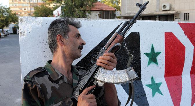 Seorang tentara bersenjata di sebuah pos pemeriksaan di pinggiran Damaskus, ibu kota Suriah.