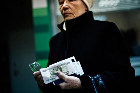 Возрасна жена со руски банкноти во рацете.