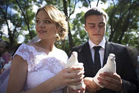 A newly wedded couple holds white doves in their hands at the unveiling ceremony of a monument dedicated to Saint Peter and Saint Fevronia, Orthodox patrons of fidelity, family and love. Source: Sergei Bobylev/TASS