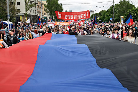 Local citizens carry a giant flag of the self-proclaimed Donetsk People's Republic (DNR or DPR) during their march marking the first anniversary of the referendum in downtown Donetsk, 11 May 2015.