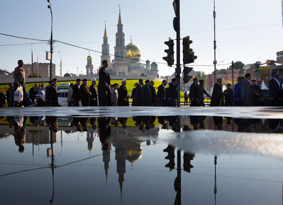 Believers head to the main mosque reflected in pool water in Moscow, Russia, early morning Wednesday, Sept. 23, 2015. Joined by the Turkish and Palestinian leaders, Russian President Vladimir Putin on Wednesday ceremoniously opened Moscow's new main mosque and spoke of the need to teach traditional Islamic values to young Russian Muslims.