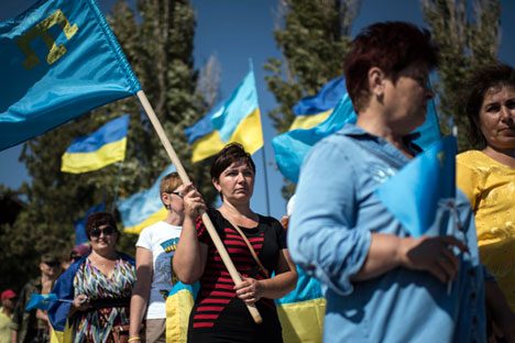 Local residents carry Ukrainian and Crimean Tatars flags in the village of Chongar, Ukraine, on Sunday, Sept. 20, 2015. The radical Right Sector group and Pro-Kiev Crimean tartars leadership organized improvised checkpoints on all three roads connecting the Ukrainian mainland and Russian-annexed Crimean peninsula, aiming to prevent trucks carrying goods to cross Russia-Ukraine border.