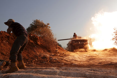 A rebel fighter of the Al-Furqan brigade covers his ears as a fellow fighter fires a vehicle's weapon during what the rebels said is an offensive to take control of the al-Mastouma army base which is controlled by forces loyal to Syria's President Bashar al-Assad near Idlib city May 17, 2015.