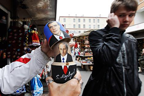 Seorang penjual menunjukkan cara membuka boneka Matryoshka dengan wajah Perdana Menteri Rusia Vladimir Putin dan Presiden Rusia Dmitry Medvedev kepada turis yang lewat di pasar suvenir di Sankt Peterburg, 26 September 2011.