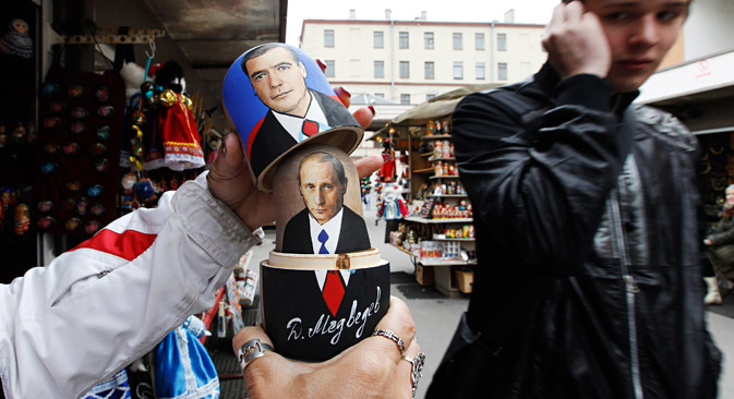 A vendor demonstrates opening a traditional Matryoshka doll, or Russian nesting doll, bearing the faces of Russian Prime Minister Vladimir Putin (underneath) and President Dmitry Medvedev to passers-by at a souvenir market in St. Petersburg September 26, 2011. Opinion polls indicate that Putin, who said on Saturday he would seek a return to the presidency after nearly four years as prime minister, is much more popular than his potential rivals and all but certain to win next March's presidential election.