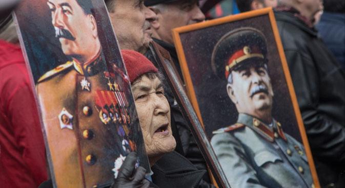 Portreti Josifa Stalina pred polaganjem cvetja na grob sovjetskega voditelja med komemoracijo ob 61. obletnici Stalinove smrti, ki je potekala na moskovskem Rdečem trgu, 5. marec 2014.