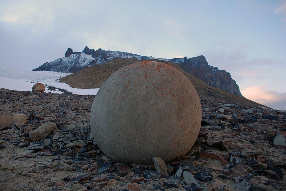 チャンプ島はロシアの北極圏でも最も遠隔で神秘的な島のひとつだ。ゼムリャフランツァヨシファ (フランツ・ヨーゼフ諸島) を構成する島の一つで、374平方キロの面積を持つこの島は、荒涼としたツンドラの地形から、各所に無作為に散在する得体の知れない球体の岩が特徴だ。この自然現象がどのような経緯で発生したのか、科学者たちは未だに正確に説明することができない。そのため、地球外からの影響によるものとするなど、ありとあらゆる法外な説が提案されている。