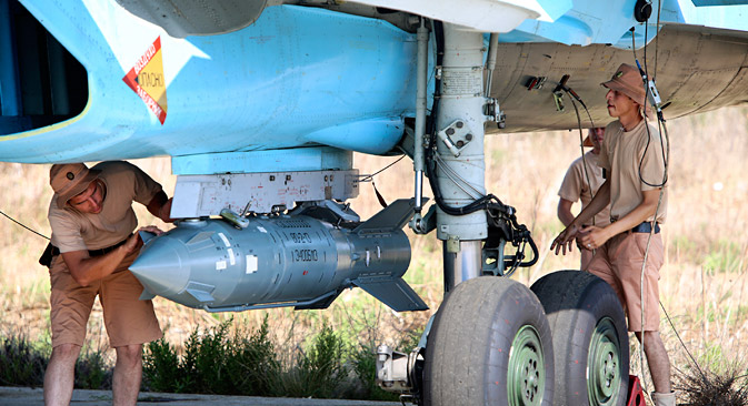In this photo taken on Saturday, Oct. 3, 2015, Russian military support crew attach a satellite guided bomb to SU-34 jet fighter at Hmeimim airbase in Syria. Source: AP
